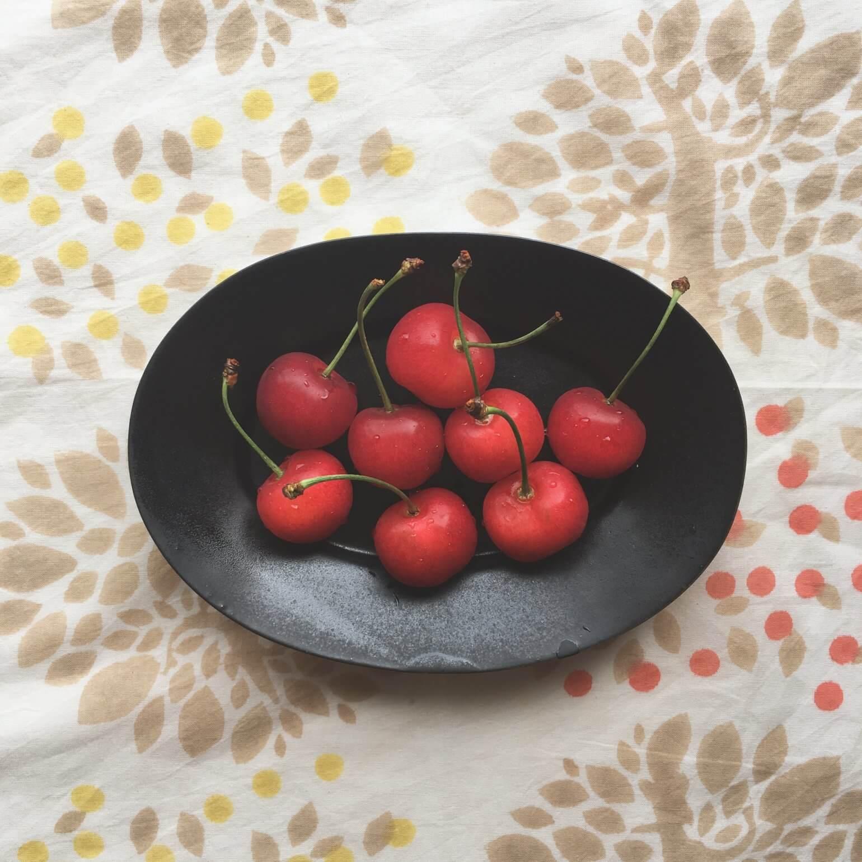 黒い皿に乗った赤いさくらんぼがMinori01柄の布の上に置いてある様子